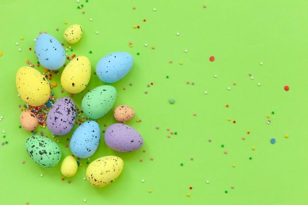 Wielobarwny jajka z konfetti na zielonym tle. koncepcja wesołych świąt.