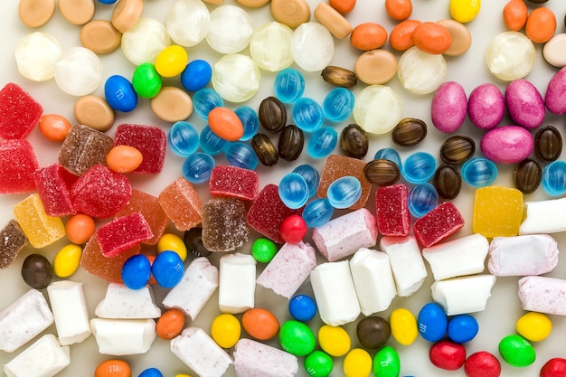 Wielobarwny karmelowe cukierki rozrzucone na tle tabeli. produkty cukrowe. kolorowe cukierki