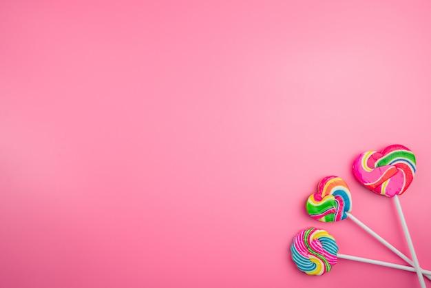 Wielobarwny lizaki na różowym tle