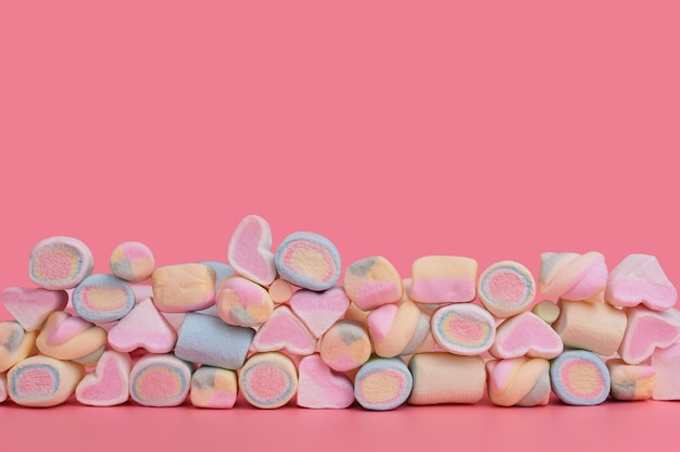Wielobarwny mieszane pianki w kilku rzędach na różowym tle. słodycze na różowo z miejscem na tekst.