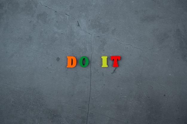 Wielobarwny napis do it składa się z drewnianych liter na szarej otynkowanej powierzchni ściany.
