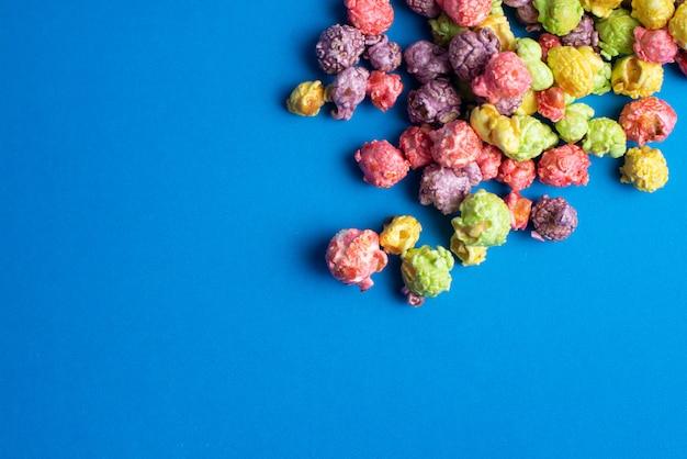 Wielobarwny popcorn o smaku owocowym na niebieskim tle. popcorn powlekany cukierkami.