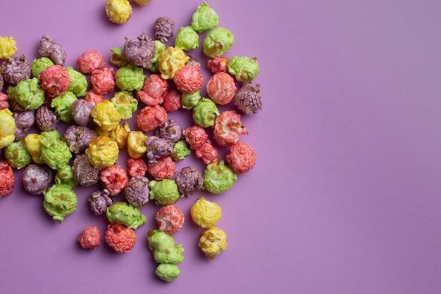 Wielobarwny popcorn o smaku owocowym na różowym tle. popcorn powlekany cukierkami.