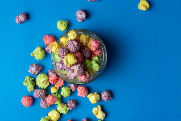 Wielobarwny popcorn o smaku owocowym w szklanych filiżankach na niebieskim tle. popcorn powlekany cukierkami.