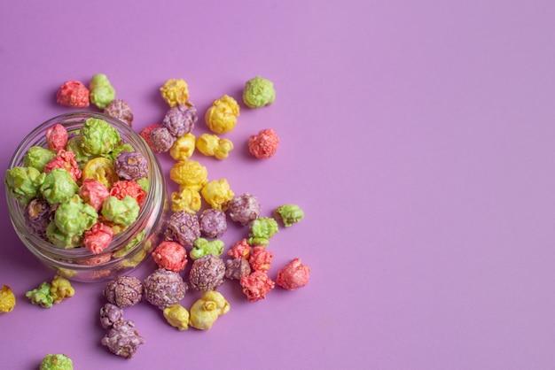 Wielobarwny popcorn o smaku owocowym w szklanych filiżankach na różowym tle. popcorn powlekany cukierkami.