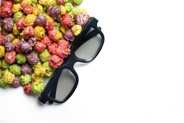 Wielobarwny popcorn o smaku owocowym z kinowymi okularami 3d na różowym tle. popcorn powlekany cukierkami. widok z góry.