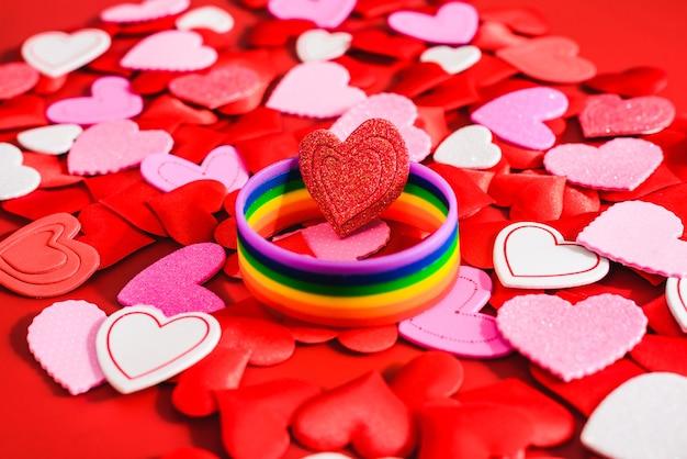 Wielobarwny symbol lgbt na czerwonych sercach