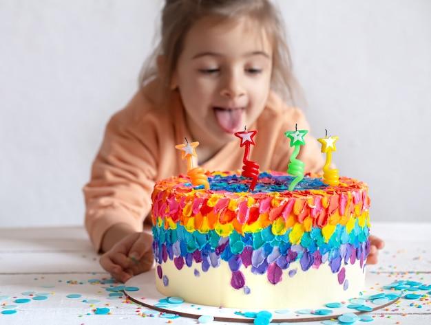 Wielobarwny tort urodzinowy ozdobiony kremem i czterema świeczkami. koncepcja urodziny.