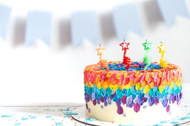 Wielobarwny tort urodzinowy ozdobiony kremem i świeczkami. koncepcja urodziny.