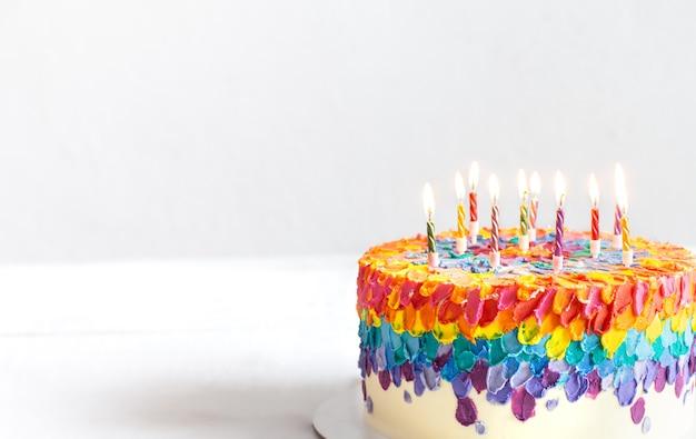 Wielobarwny tort urodzinowy ozdobiony płonącymi świeczkami. koncepcja życzenia urodzinowe.