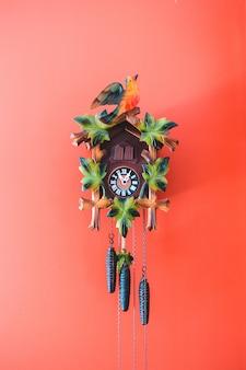 Wielobarwny zegar z kukułką na czerwonej ścianie