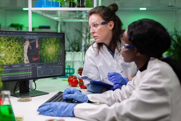 Wieloetniczna grupa biologów analizująca eksperyment roślinny na komputerze