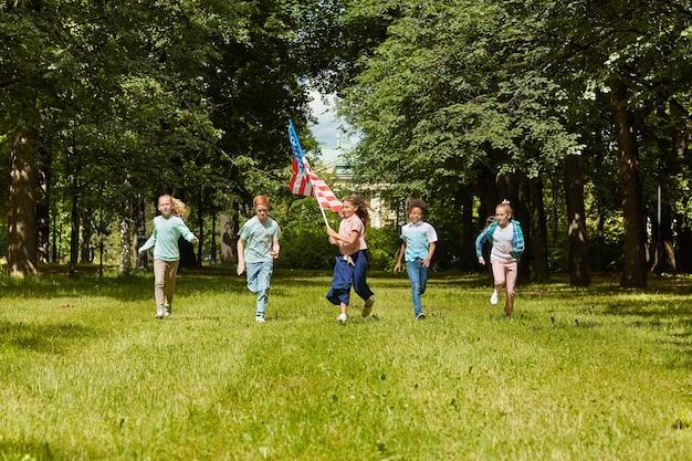 Wieloetniczna grupa dzieci biegających po zielonym trawniku z dziewczyną machającą amerykańską flagą