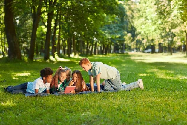 Wieloetniczna grupa dzieci korzystających z cyfrowego tabletu, leżąc na zielonej trawie w parku na świeżym powietrzu oświetlonym światłem słonecznym