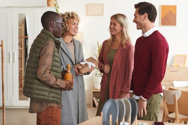 Wieloetniczna grupa eleganckich dorosłych ludzi witających się nawzajem i wymieniających się prezentami, witając gości na przyjęciu w pomieszczeniu