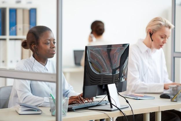 Wieloetniczna grupa kobiet operatorów call center korzystających z komputerów w miejscu pracy, skupia się na młodej afroamerykance noszącej zestaw słuchawkowy na pierwszym planie