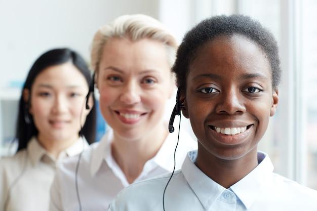 Wieloetniczna grupa kobiet operatorów call center patrząc stojących w rzędzie, skupić się na uśmiechniętej african-american kobiety noszącej zestaw słuchawkowy na pierwszym planie