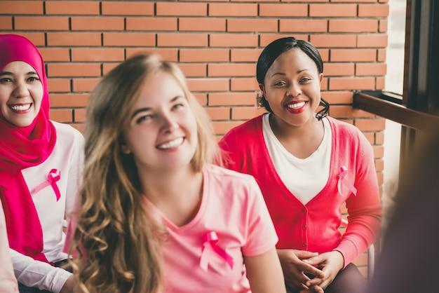 Wieloetniczna grupa kobiet spotykających się na kampanię świadomości raka piersi