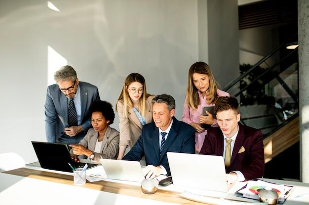 Wieloetniczna grupa ludzi biznesu pracujących razem i przygotowujących nowy projekt spotkania w biurze
