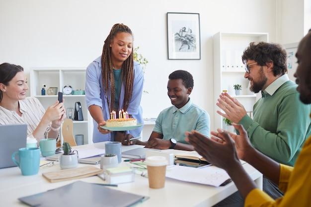 Wieloetniczna grupa ludzi obchodzi urodziny w biurze, skupia się na uśmiechniętej kobiecie przynoszącej tort młodemu afroamerykaninowi