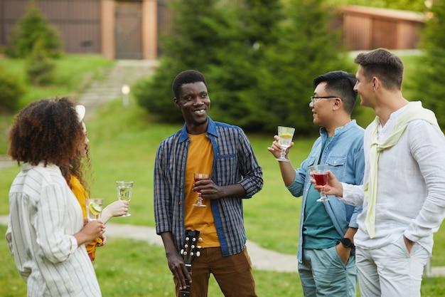 Wieloetniczna grupa ludzi pijących koktajle i rozmawiających podczas letnich imprez plenerowych