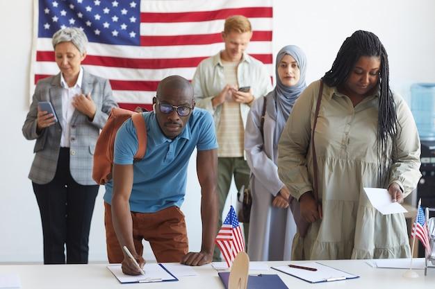 Wieloetniczna grupa ludzi rejestrujących się w lokalu wyborczym udekorowanym amerykańskimi flagami w dniu wyborów, skup się na afrykańskim człowieku podpisującym karty do głosowania i skopiuj miejsce