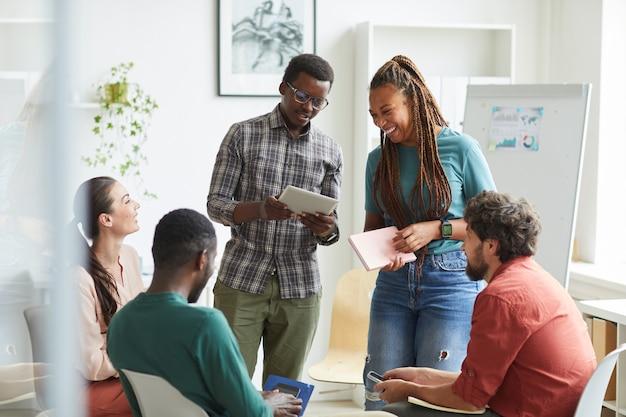 Wieloetniczna grupa ludzi siedząca w kręgu podczas omawiania projektu biznesowego w biurze, skup się na uśmiechniętej afroamerykańskiej kobiecie rozmawiającej z koleżanką stojącą