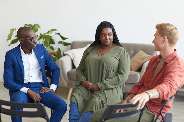 Wieloetniczna grupa ludzi siedząca w kręgu podczas spotkania grupy wsparcia i omawiająca problemy, kopia przestrzeń
