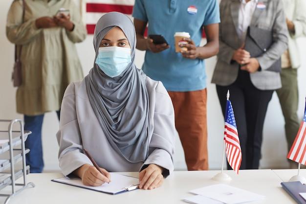 Wieloetniczna grupa ludzi stojących w rzędach i noszących maski w lokalu wyborczym w dniu wyborów, podczas rejestracji do głosowania skup się na młodej arabce, skopiuj miejsce