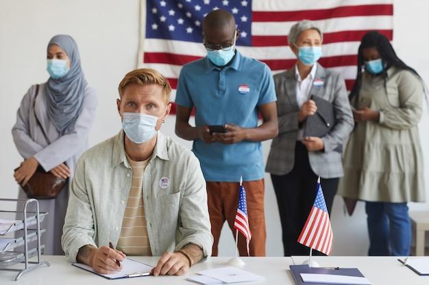 Wieloetniczna grupa ludzi stojących w rzędach i noszących maski w lokalu wyborczym w dniu wyborów, podczas rejestracji do głosowania skup się na młodym mężczyźnie