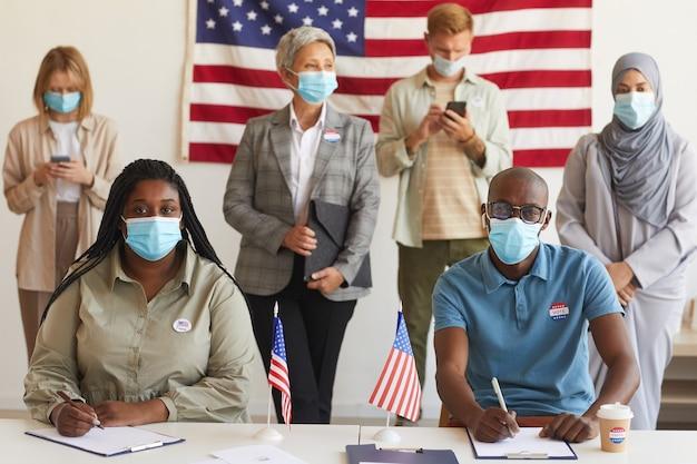 Wieloetniczna grupa ludzi stojących w rzędach i noszących maski w lokalu wyborczym w dniu wyborów, podczas rejestracji do głosowania skup się na parze afroamerykańskiej