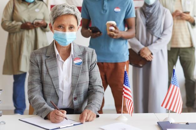 Wieloetniczna grupa ludzi stojących w rzędach i noszących maski w lokalu wyborczym w dniu wyborów, skup się na nowoczesnej starszej kobiecie podczas rejestracji do głosowania, skopiuj miejsce