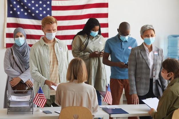 Wieloetniczna grupa ludzi stojących w rzędach i noszących maski w lokalu wyborczym w dniu wyborów