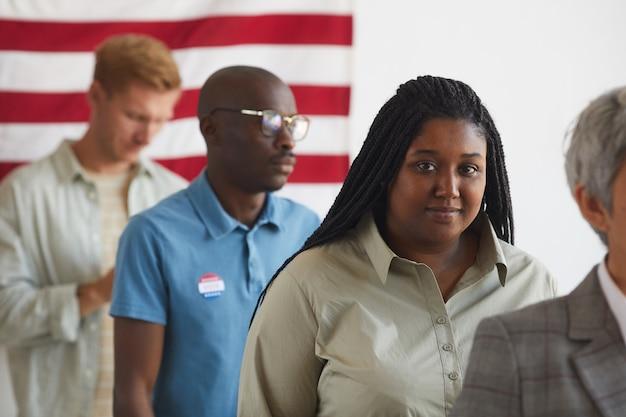 Wieloetniczna grupa ludzi stojących w rzędzie w lokalu wyborczym w dniu wyborów, skup się na uśmiechniętej afroamerykańskiej kobiecie, skopiuj miejsce