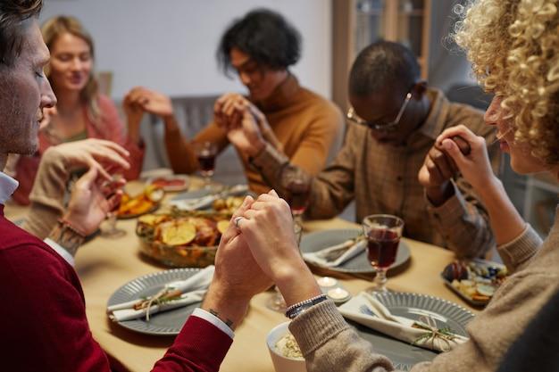 Wieloetniczna grupa ludzi trzymających się za ręce podczas modlitwy na kolacji dziękczynnej z przyjaciółmi i rodziną, skup się na pierwszym planie,
