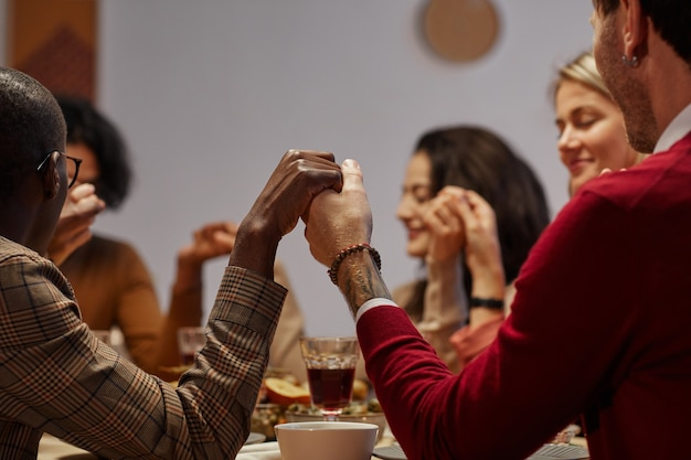 Wieloetniczna grupa ludzi trzymających się za ręce w modlitwie na kolacji dziękczynnej z przyjaciółmi i rodziną, skupienie się na pierwszym planie,