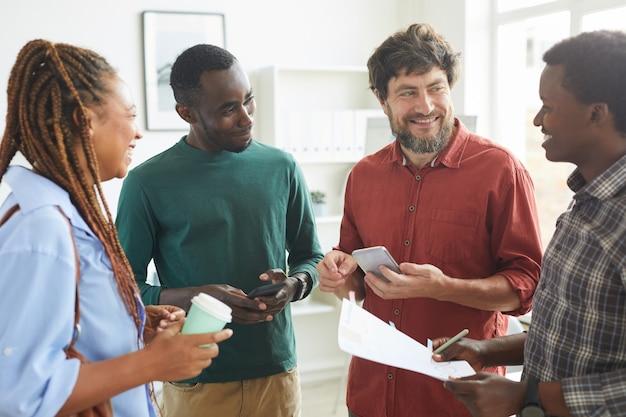 Wieloetniczna grupa ludzi ubranych w codzienne stroje i uśmiechających się wesoło, omawiając pracę stojącą w biurze