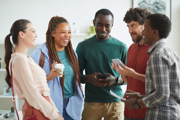 Wieloetniczna grupa ludzi ubranych w zwykłe stroje i wesoło śmiejących się podczas rozmowy w biurze