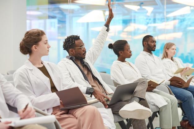 Wieloetniczna grupa ludzi w fartuchach laboratoryjnych siedzących w rzędzie na widowni na seminarium medycznym, skupiająca się na afroamerykanie podnoszącym rękę, by zadać pytanie, kopiującym przestrzeń