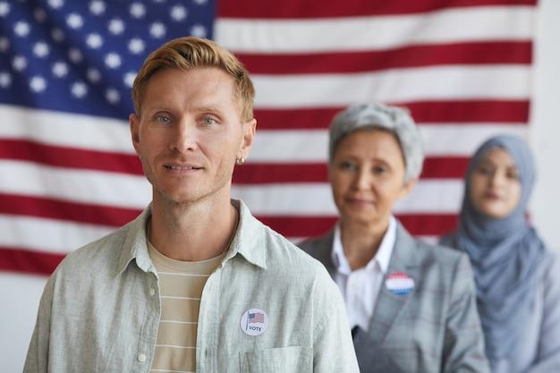 Wieloetniczna grupa ludzi w lokalu wyborczym w dniu wyborów, skup się na współczesnym mężczyźnie z naklejką i głosuję, skopiuj miejsce