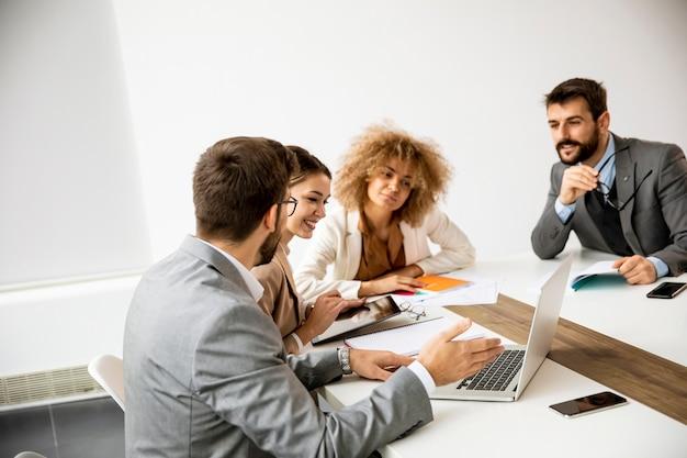 Wieloetniczna grupa młodych ludzi biznesu pracujących razem i przygotowujących nowy projekt na spotkaniu w biurze