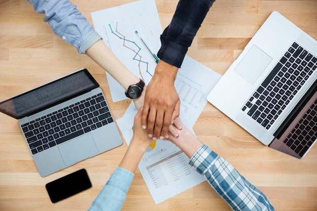 Wieloetniczna grupa młodych ludzi pracujących z laptopami i łączących się w ręce