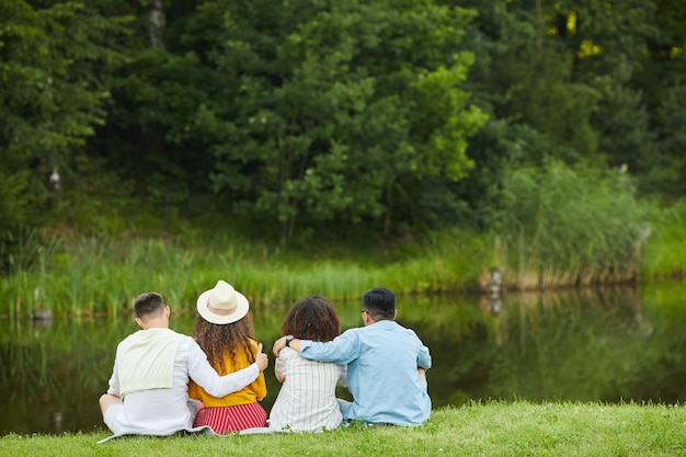 Wieloetniczna grupa młodych ludzi siedzących nad wodą i cieszących się wakacjami w lecie