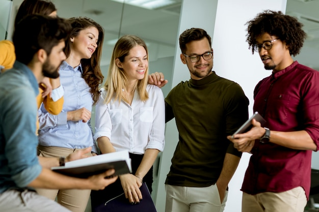 Wieloetniczna grupa młodych ludzi stojących w nowoczesnym biurze i burzy mózgów