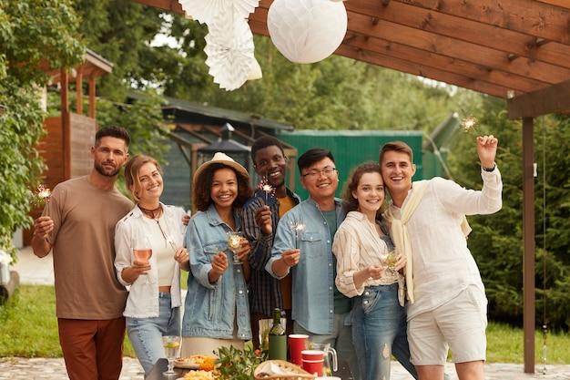 Wieloetniczna grupa młodych ludzi trzymających zimne ognie, uśmiechając się i ciesząc się letnią imprezą na tarasie