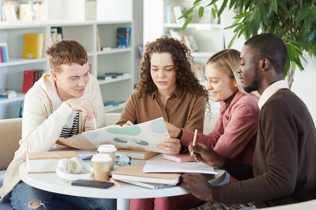 Wieloetniczna grupa młodych ludzi uczących się razem siedząc przy stole w bibliotece uczelni i pracując nad projektem grupowym,