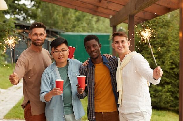 Wieloetniczna grupa młodych mężczyzn trzymających zimne ognie, uśmiechając się i ciesząc się letnią imprezą na tarasie