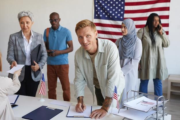 Wieloetniczna grupa osób rejestrujących się w lokalu wyborczym ozdobionym amerykańskimi flagami w dniu wyborów, skup się na uśmiechniętym mężczyźnie podpisującym karty do głosowania i skopiuj miejsce