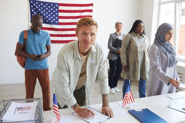 Wieloetniczna grupa osób rejestrujących się w lokalu wyborczym udekorowanym amerykańskimi flagami w dniu wyborów, skupienie się na podpisywaniu kart do głosowania przez młodego mężczyznę i skopiowanie miejsca