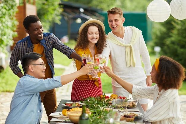 Wieloetniczna grupa przyjaciół brzęczących szklankami przy kolacji na świeżym powietrzu na imprezie letniej